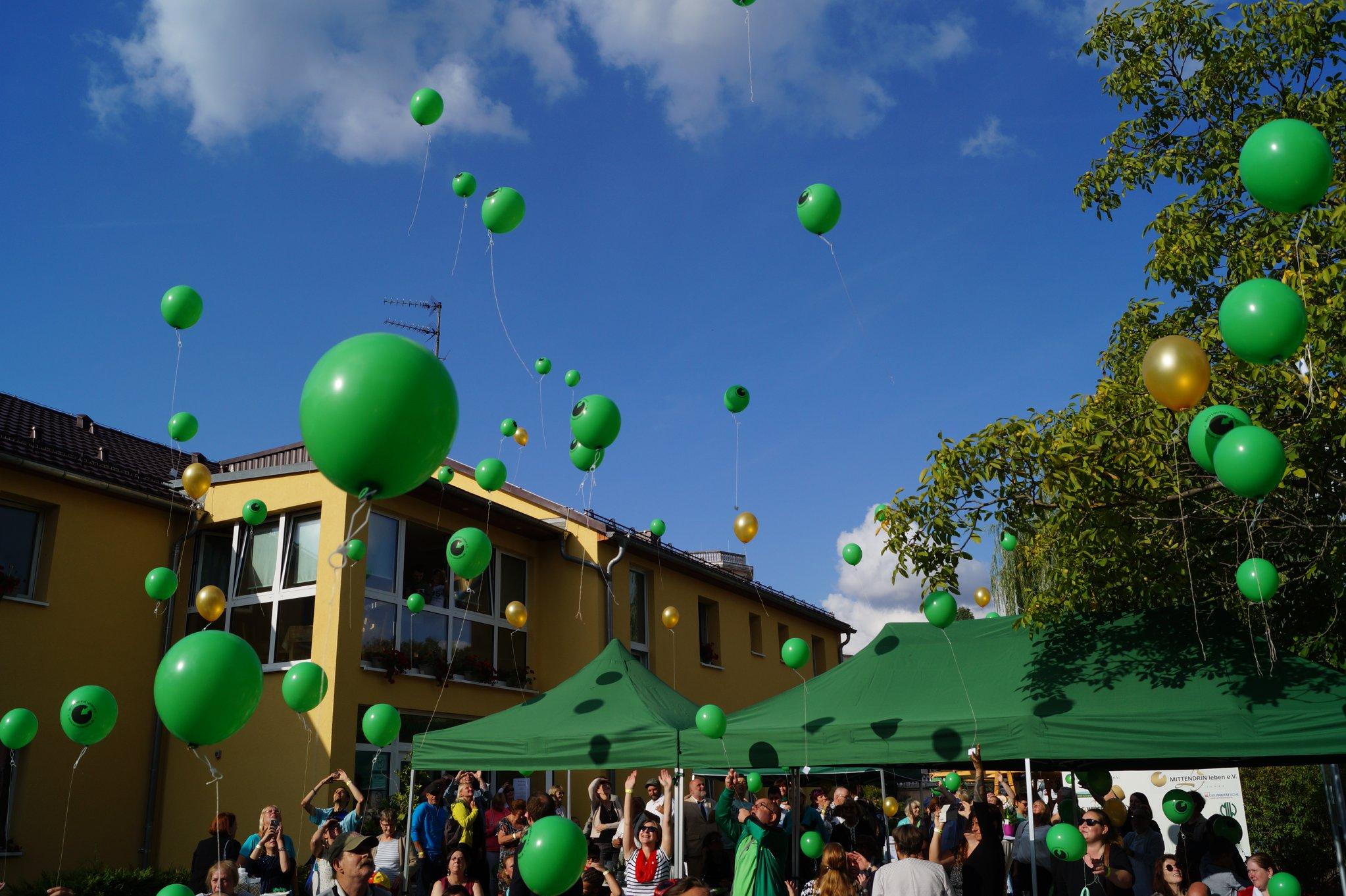 Menschen lassen grüne Luftballons vor dem Stadtteilzentrum Kaulsdorf steigen