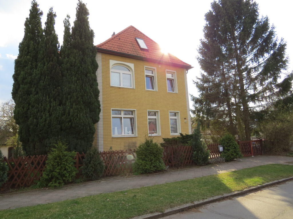 Villa MITTENDRIN - Betreutes Jugendwohnen - Zweistöckiges Haus mit Spitzdach - gelbe Fassade, rotes Dach - rechts und links vom Haus stehen Bäume, über dem Dach blitzt die Sonne ins Objektiv