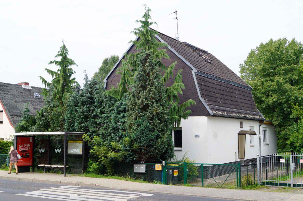 Intensiv betreutes Einzelwohnen Hönower Straße. Einfamilienhaus mit weißer Fassade und dunklem Dach mit Garten. Vor dem Haus stehen Nadelbäume