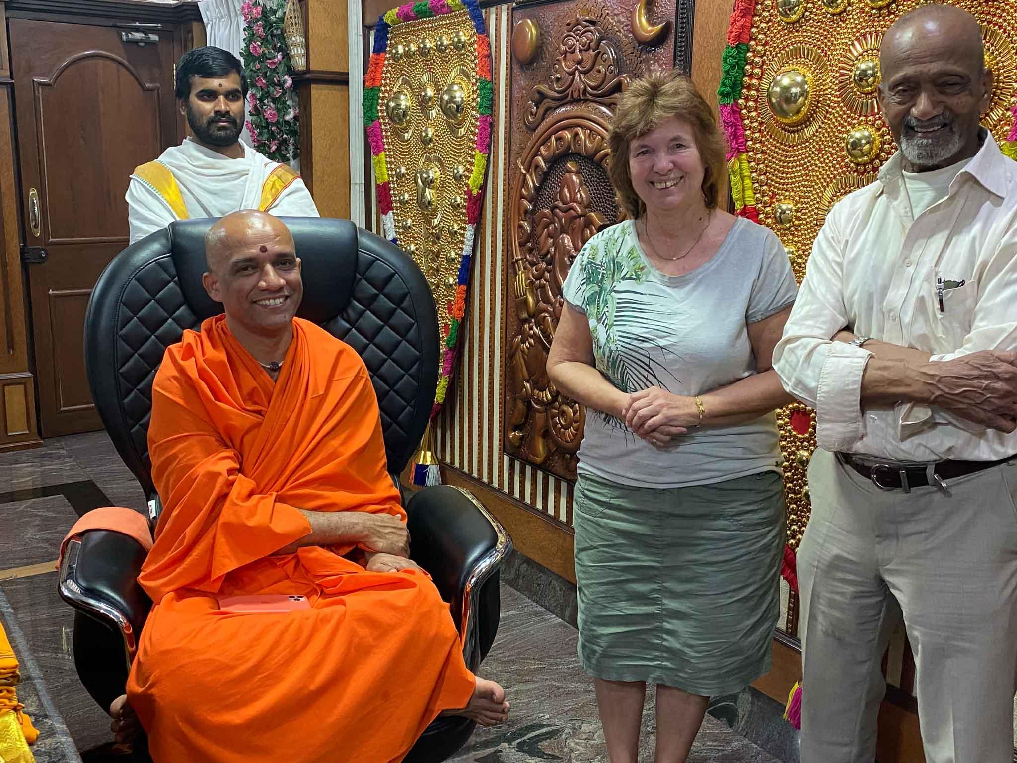 Internationale Hilfe Audienz beim Swamichi. 1 Frau und 2 Männer stehen neben dem in orange gegkleideten Swamichi