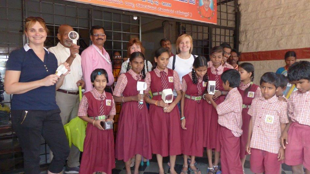 Internationale Hilfe: personengruppe vor der Schule. Kinder tragen weinrote Schuluniformen