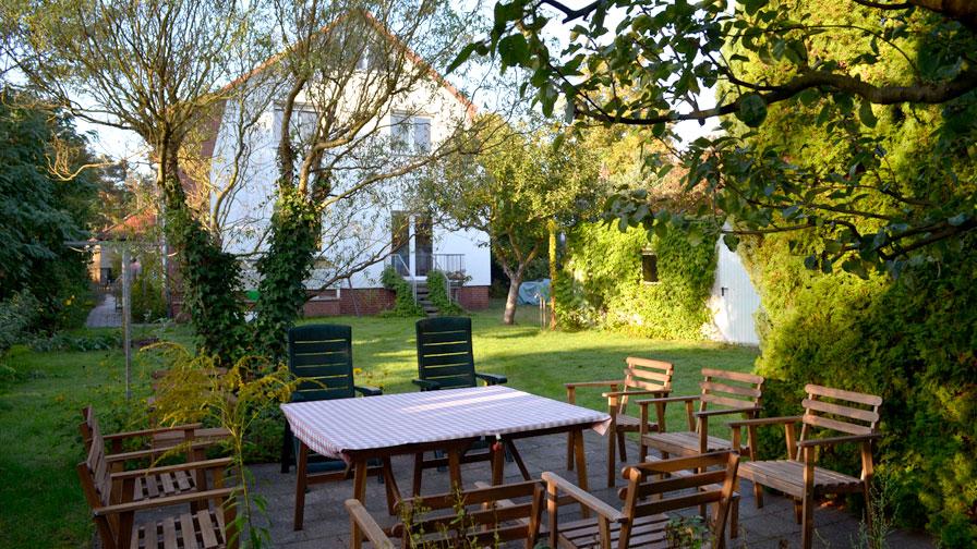 Garten TWG Rüstenallee mit Tisch mit 8 Gartenstühlen, Rasenfläche und Bäumen