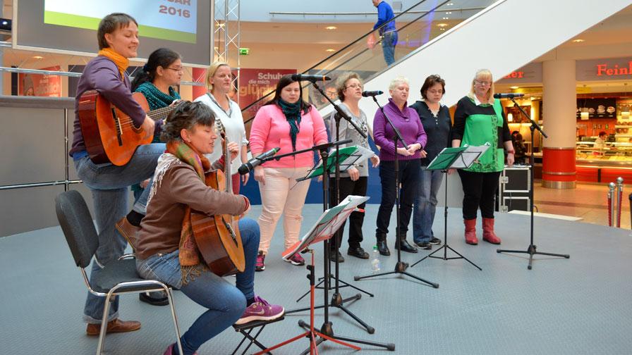 Singegruppe: Im Einkaufszentrum Eastgate singt die Singegruppe auf einer Veranstaltungsfläche. Es sind 6 Sängerinnen und zwei Gitarrenspielerinnen zu sehen. Im Hintergrund Geschäfte und eine Rolltreppe