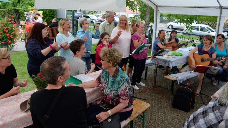 Singegruppe: In einem kleinen Festzelt singt die Singegruppe. Gäste sitzen auf Bierbänken und hören zu