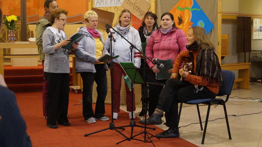 Singegruppe: 5 Sängerrinnen stehend und eine Gitarrenspielerin sitzend auf einer kleinen Veranstaltungsfläche