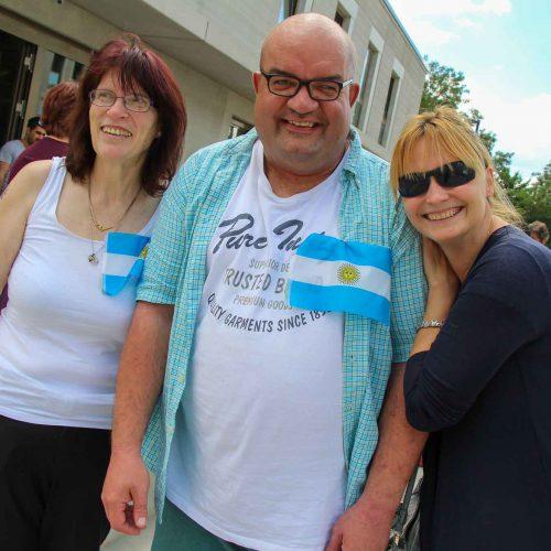 3 Personen beim Tischkicker-Event. 2 Frauen und 1 Mann bilden zusammen das Team Argentinien. Sie tragen die Landesflagge