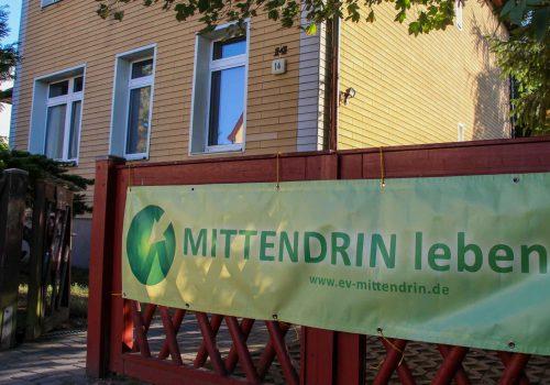 Foto von der Villa. Am roten Gartentor hängt ein Banner von MITTENDRIN leben e.V. im Hintergrund das Haus mit der gelben Fassade