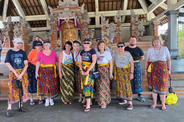 Betreutes Reise nach Bali: Gruppenfoto in einem Tempel. Alle tragen traditonelle Röcke