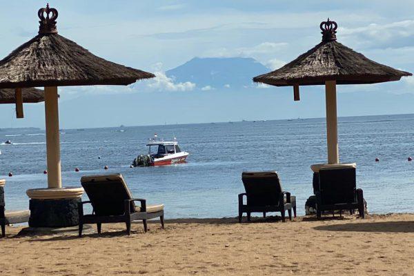 Betreute Reise Bali. Strand mit 2 Schirmen aus Stroh und Sonnenliegen. Im Hintergrund fährt ein Boot.