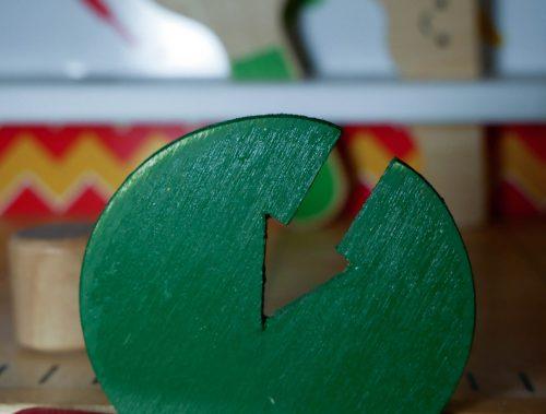 Einzelfallhilfe: Eine Werkbank für Kinder. Im Schraubstock im Vordergrund ist ein grüner Holzkreis mit einem eingesäckten Pfeil befestigt. Im Hintergrund sieht man verschwommen eine Holzsäge und einen Holzmaulschlüssel, die jeweils einen lächelnden Smiley aufgedruckt haben.