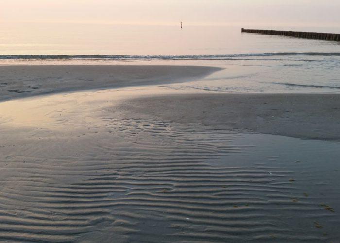 Zingst. Ein leicht überfluteter Strand im Abendlicht